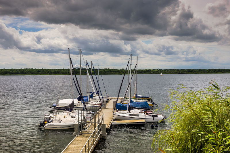Yachts moored on Markkleeberger See (Markkleeberger Lake) in the Markkleeberg suburb of Leipzig in Saxony, Germany. Dark Clouds Markkleeberger Lake Travel Cliuds Cloud - Sky Day Destination Lake Markkleeberger See Moored Nature Nautical Vessel No People Outdoors Scenics Sky Tranquility Transportation Travel Destinations Water Yacht