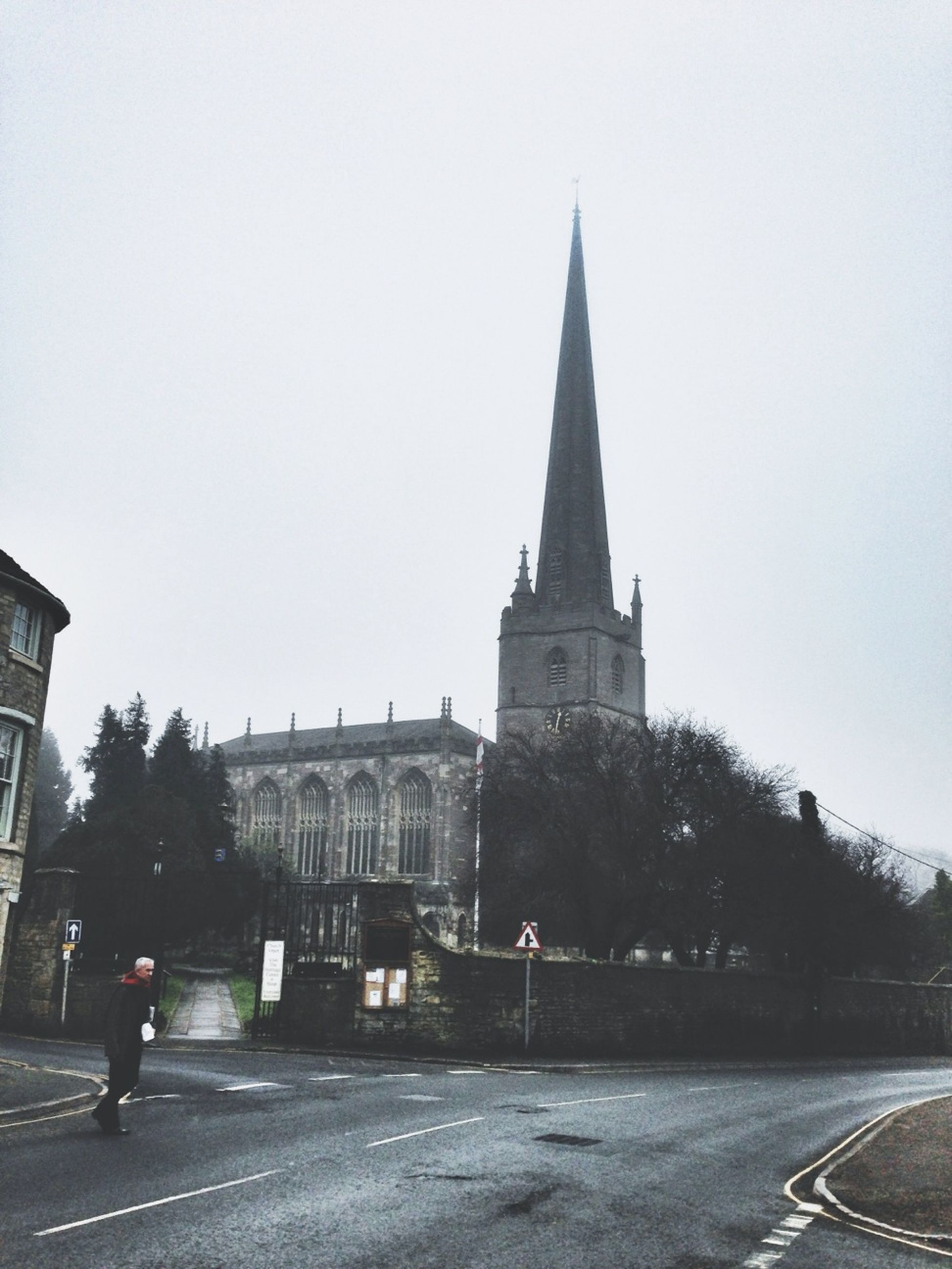 building exterior, architecture, clear sky, built structure, church, road, religion, transportation, place of worship, street, copy space, spirituality, the way forward, sky, incidental people, car, tree, road marking