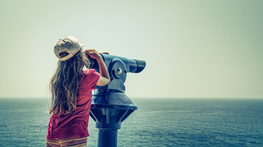 Young long blond hair girl wearing red shirt and white cap observing a sea via a blue telescope Casual Clothing Clear Sky Day Holding Horizon Over Water Leisure Activity Long Hair Nature One Person Outdoors Real People Rear View Sea Sky Standing Water
