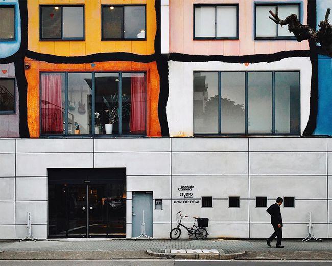 Man Walking On Sidewalk By Building In City