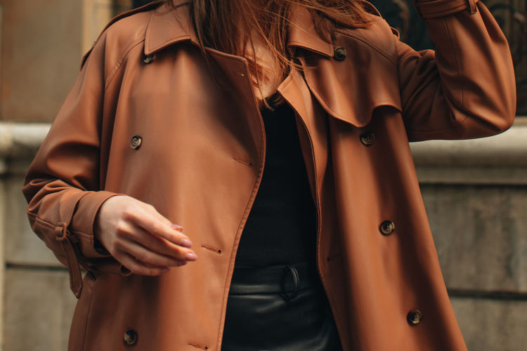 Cropped figure of young woman wearing stylish brown overcoat street casual autumn concept.