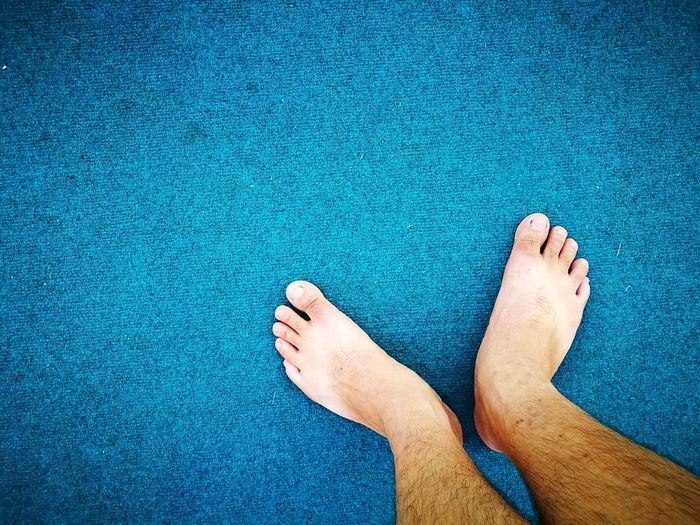 Low section of man standing on blue carpet