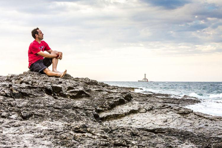 Full length of man sitting on rock at beach against sky