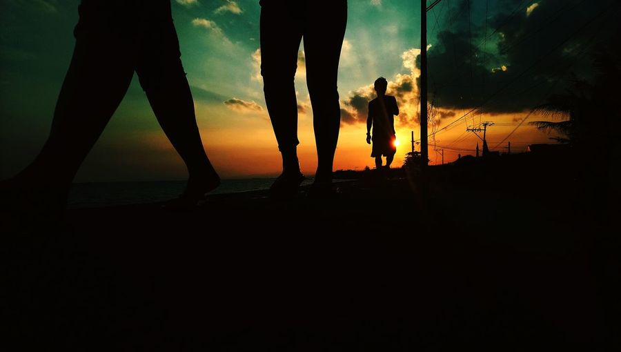 Low Section Of Silhouette People Walking Against Sky During Sunset