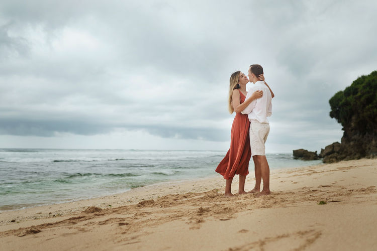 Couple standing on beach against sea