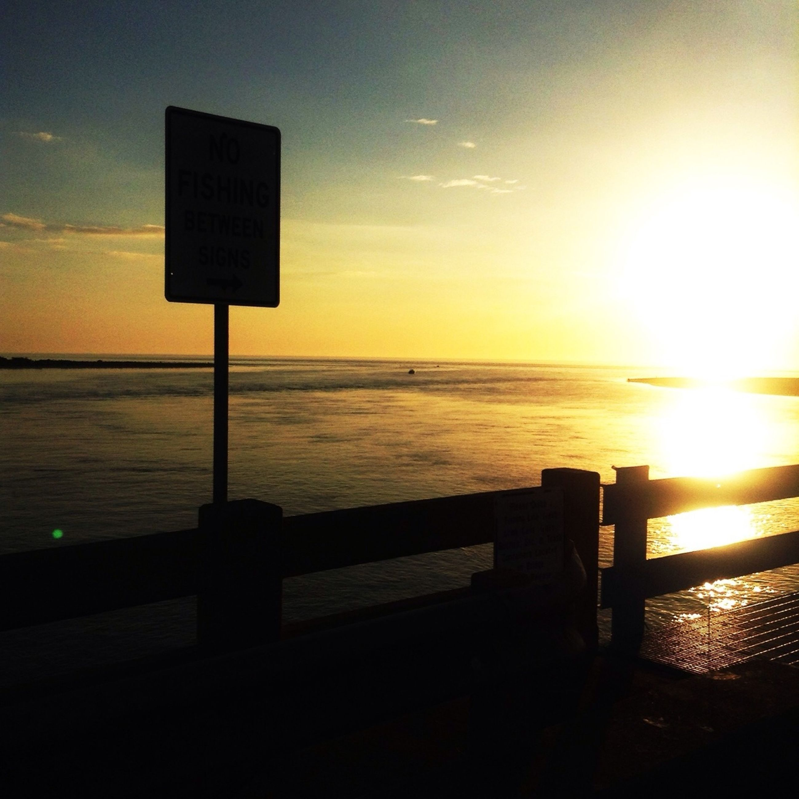 sunset, sea, water, horizon over water, guidance, communication, scenics, text, tranquility, sky, tranquil scene, orange color, western script, information sign, beauty in nature, beach, silhouette, sun, sign, nature