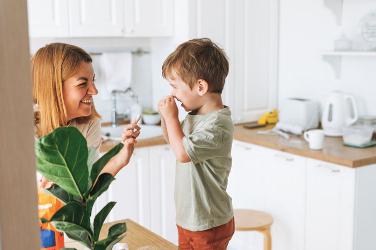 Young woman mother and toddler boy son have fun while cooking with flour at table in bright kitchen