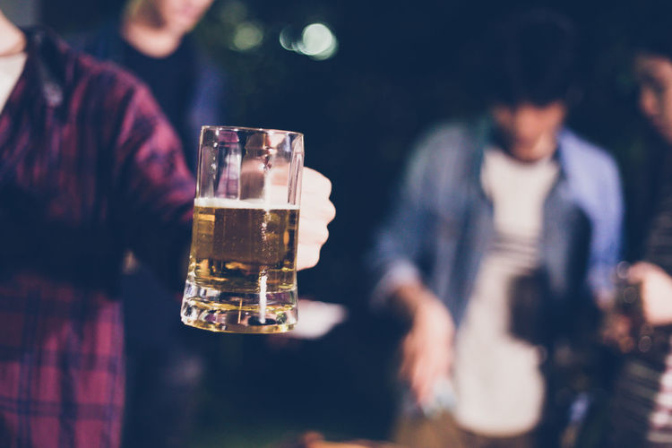 Midsection Of Man Holding Beer Glass At Night