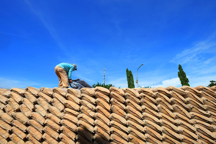 Low angle view of man working on staked sacks against blue sky
