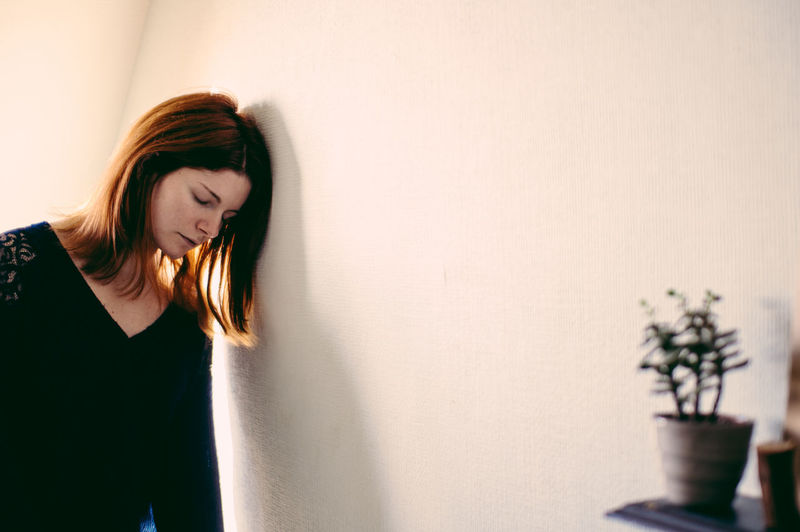 Depressed woman leaning on wall at home