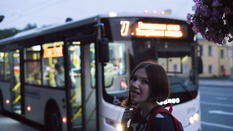 Portrait Of Young Woman Sticking Out Tongue Against Bus In City