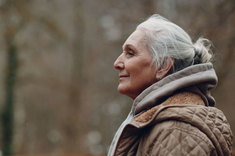 Portrait of a smiling senior woman looking away outdoors