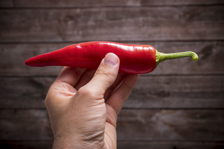 Cropped hand holding red chili pepper over wooden table