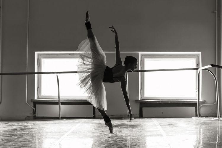 Full length of young ballet dancer balancing on floor
