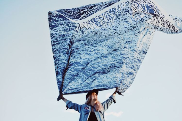 Low angle view of woman holding scarf against sky