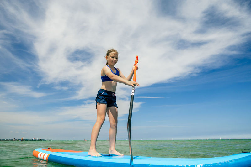 Full length of woman standing on sea against sky