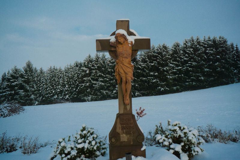 View of cross statue against trees in winter