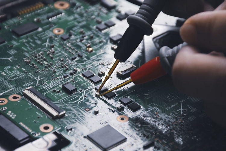 Technician checking laptop circuit board with multimeter