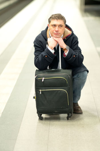 Man with luggage sitting at railroad station platform