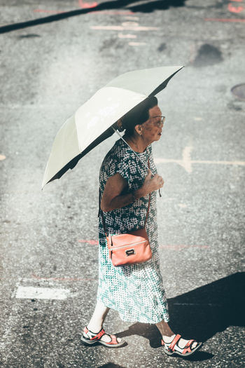 Young woman holding umbrella while standing on road