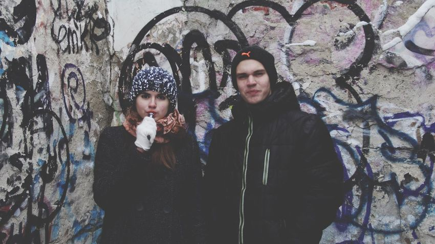Graffiti Real People Lifestyles Two People Leisure Activity Bonding Boys Looking At Camera Front View Togetherness Portrait Winter Outdoors Standing Building Exterior Day Warm Clothing Cold Temperature Young Women