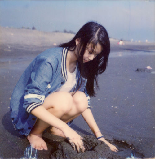 Girl Playing With Sand On Shore At Beach
