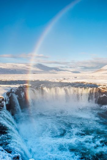 Scenic view of rainbow over waterfall against sky