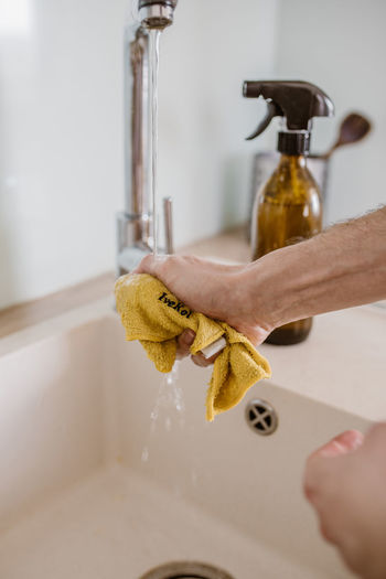 Close-up of hand holding faucet in bathroom