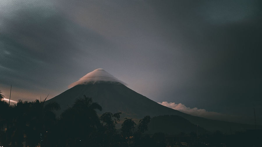 Scenic view of snowcapped mountains against sky . the mayon volcano under umbrella clouds