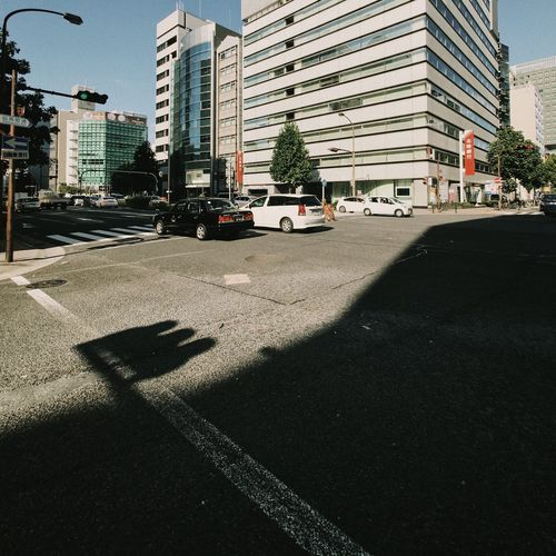 Cars on road by city against sky