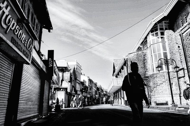 Rear view of people walking on street amidst buildings in city