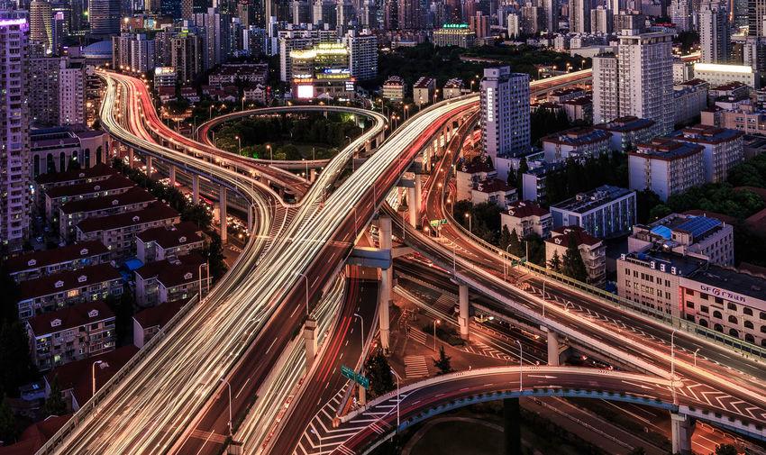 Light Trails On Bridges Amidst Cityscape