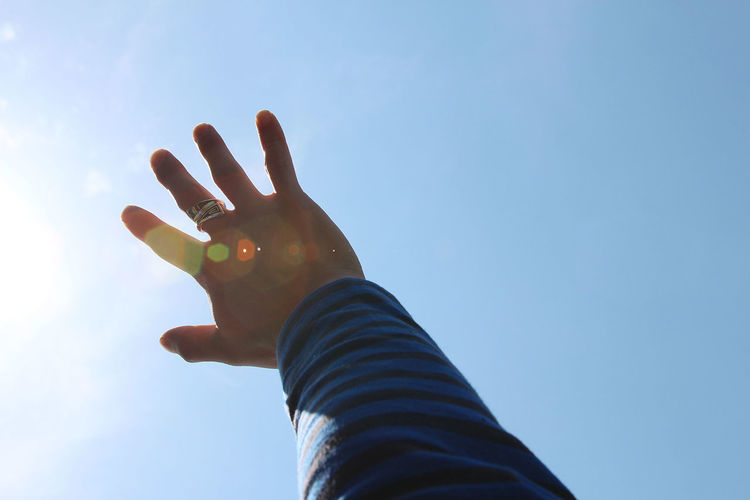 Cropped hand against clear blue sky during sunny day