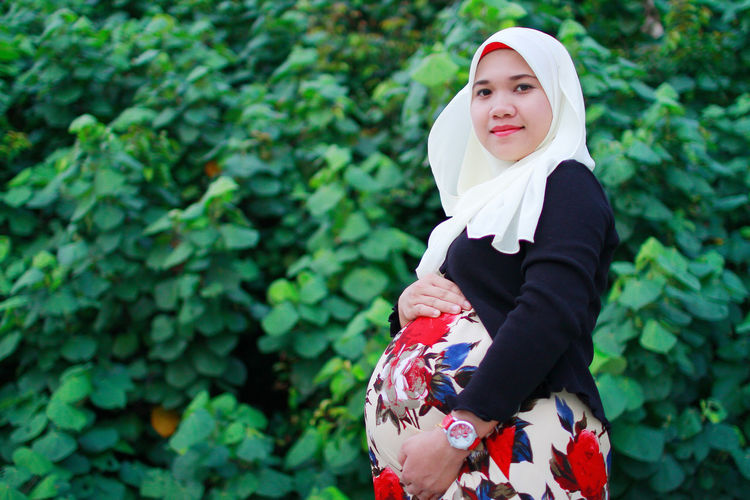 Portrait of smiling pregnant woman with hand on stomach standing against plants