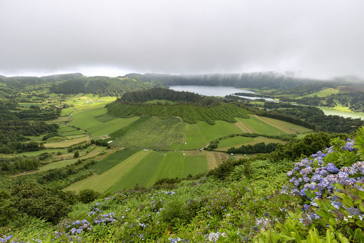 Wide Angle view of the Sete Cidades Caldera with two smaller calderas and lakes in the distance on Sao Miguel. Sao Miguel Azores Açores Sete Cidades Hike Trek Trail Landscape Caldera Crater Lagoa Azul Verde Seca Alferes Flowers Hydrangea Ginetes Varzea Clouds Fog Travel Tourism Destination