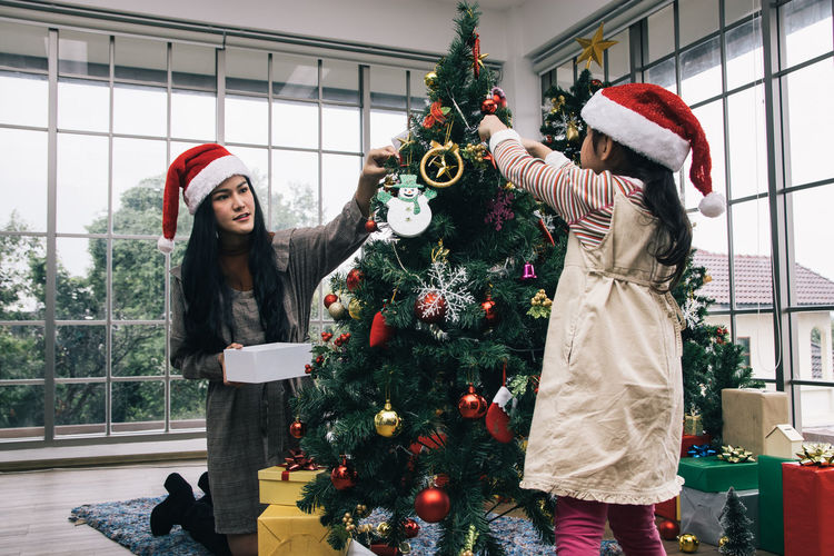 Mother with daughter decorating christmas tree at home