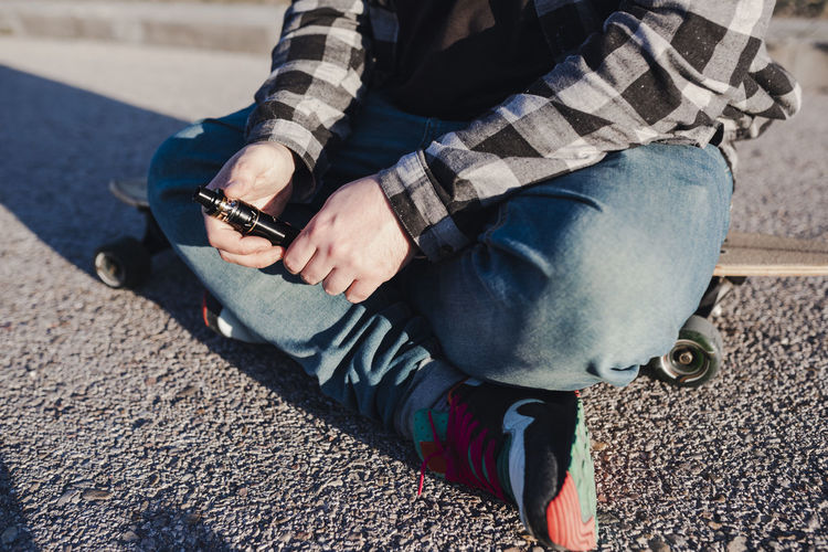 Low section of man using mobile phone while sitting outdoors