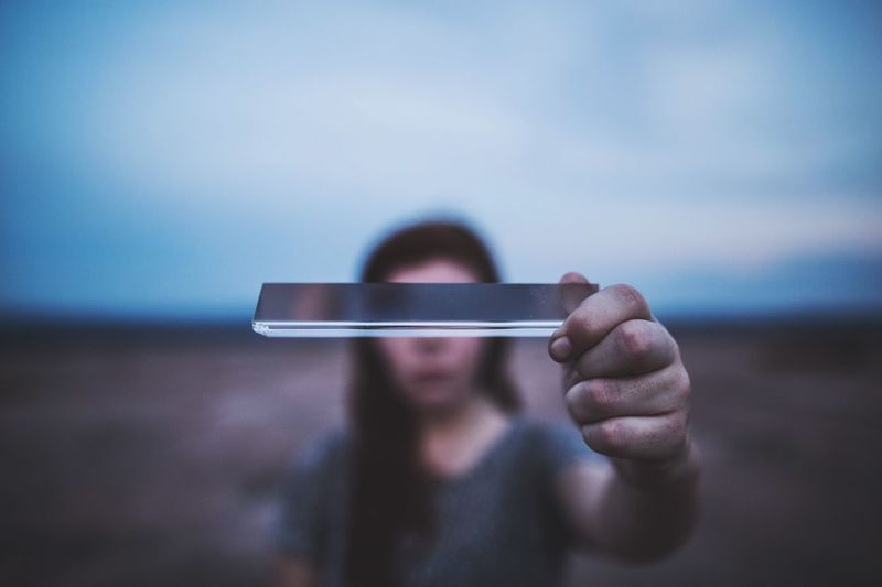Close-Up Of Woman Holding Smart Phone Against Sky