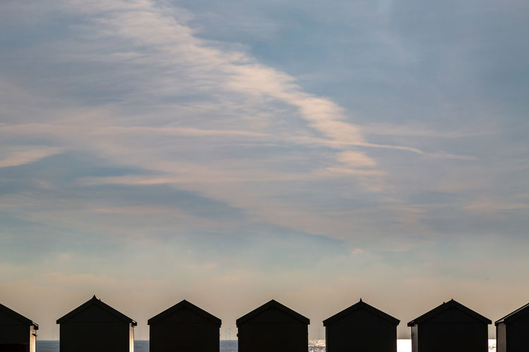 Silhouetted beach huts at the seaside, with the sea behind