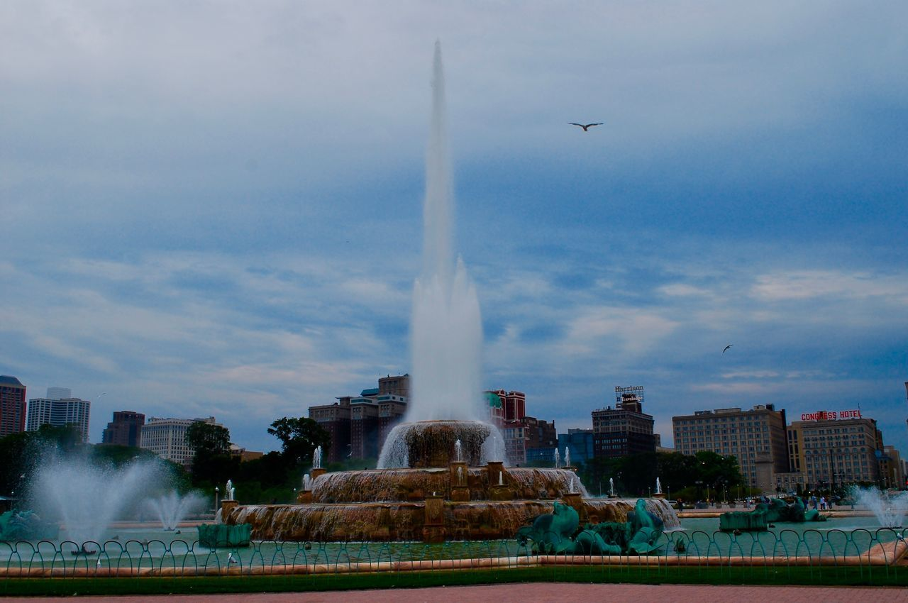 fountain, water, motion, spraying, architecture, built structure, sky, cloud - sky, splashing, outdoors, building exterior, day, city, no people, nature