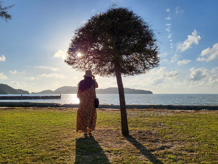 Woman standing by tree on beach against sky