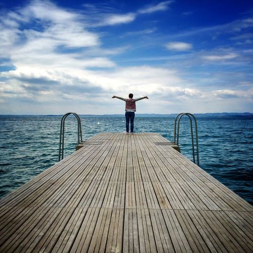 Full length of woman standing on pier on sea against sky
