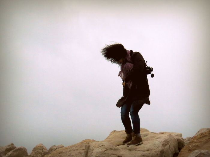 Full Length Of Woman Standing On Rock Against Sky During Windy Day