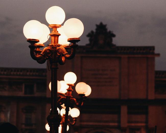 Illuminated Lamp Posts Against Building At Dusk