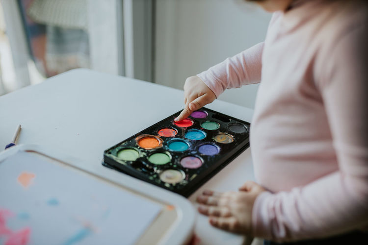 Midsection of girl touching paint in palette