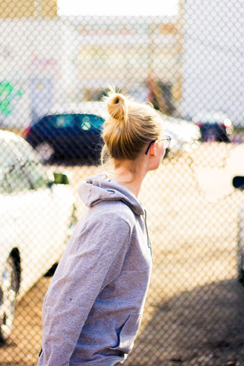 Side view of young woman standing on chainlink fence