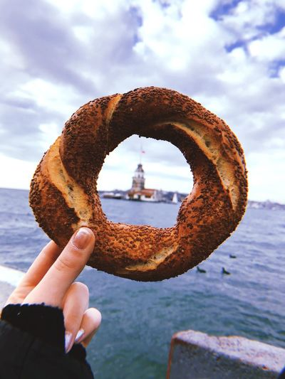 Cropped hand of woman holding baked pastry item against sea