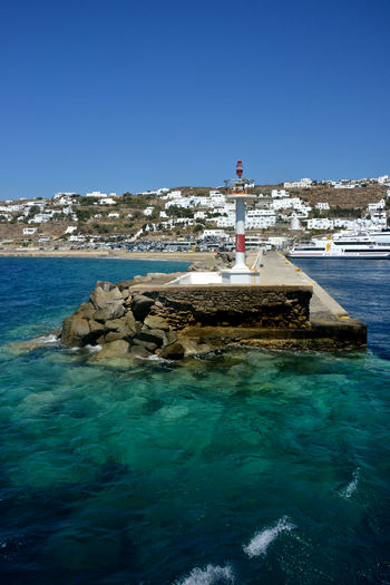seaside view of town in Mykonos with navigation lights in the pier and blue sea. No People Outdoors Scenics - Nature Lighthouse Nature Built Structure Sea Building Exterior Rock - Object Mykonos,Greece Pier Port Seaside View Navigation Light Guidance Day Sky Travel Marina Turquoise Water Water Maritime Nautical Nautical Equipment Rock Yacht Travel Destinations