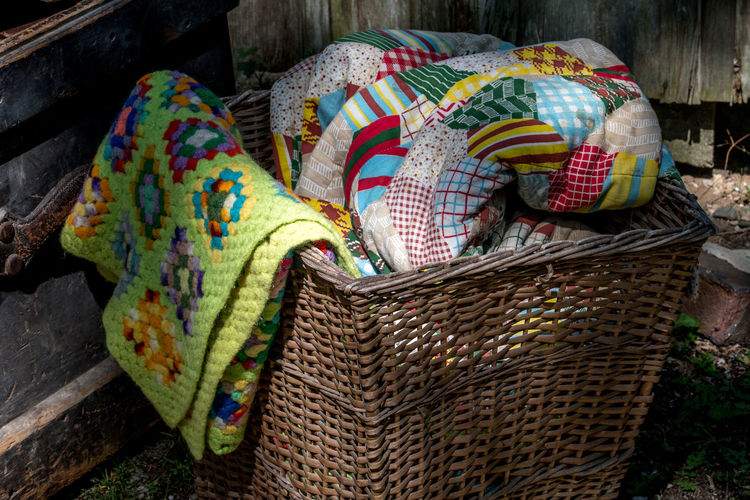 old wicker basket of retro blankets and hand made quilts Retro Architecture Art And Craft Basket Basket Basket Weave Blanket Close-up Clothing Container Craft Creativity Day High Angle View Material Multi Colored No People Outdoors Pattern Pillow Quilt Representation Still Life Textile Wicker Capture Tomorrow