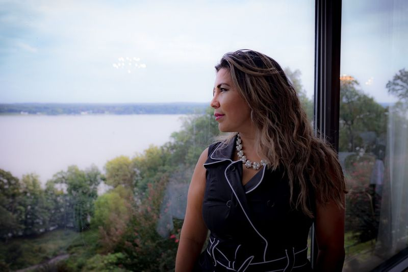 Portrait of beautiful young woman looking away against sky